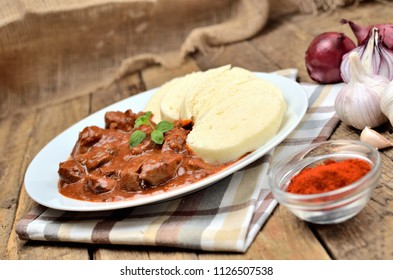 Pork goulash meat with dumplings on white plate, cutlery, garlic, onion, pepper, tablecloth in the background - typical Czech food
