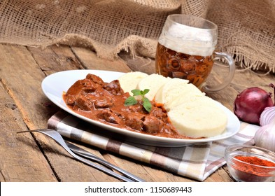 Pork goulash meat with dumplings on white plate, cutlery, cold beer, garlic, onion, pepper, tablecloth in the background - typical Czech food