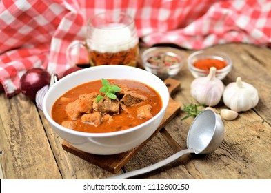 Pork goulash with pieces of meat in a bowl, garlic, pepper, onion, glass with cold beer, ladle and red checkered tablecloth in the background