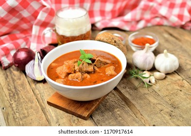 Pork goulash with pieces of meat in a bowl, garlic, pepper, onion, glass with cold beer and red checkered tablecloth in the background