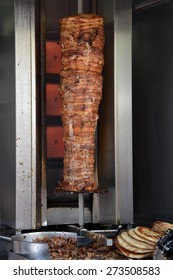 Pork gyros on vertical broiler rotisserie machine and grilled pita souvlaki bread. Traditional greek fast food.
