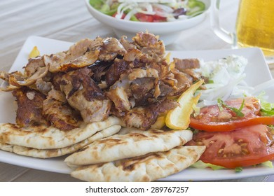 Pork gyros portion served on a plate with vegetables and salad