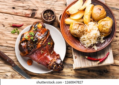Pork knuckle on rustic table.Roasted pork knuckle with potatoes