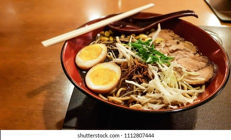 Pork Lamen on the bowl with traditional yellow yolks, spring onions, shoyuy sauce and pork. Traditional japanese pasta.