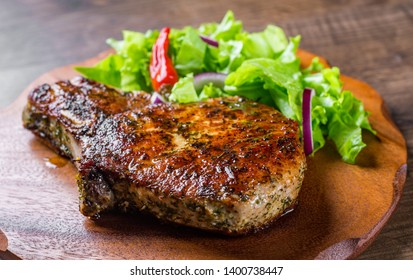 Pork Loin chops marinated meat Steak with vegetables slad on wooden table background