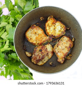 Pork loin in a frying pan with parsley
