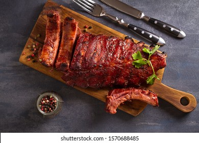 Pork loin ribs served on chopping board. View from above, top