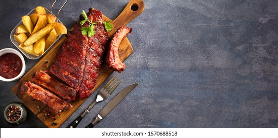 Pork loin ribs served on chopping board and potato wedges. View from above, top. Copy space