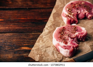 Pork loin steaks with ground spices on baking paper