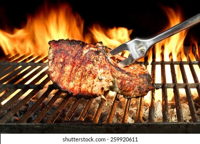 Pork Meat Chop Cooked On The Barbecue Grill. Flame Of Fire In The Background. You can see more grilled food, picnic and party scene in my public set.