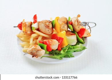 Pork meat skewers with french fries and ruccola leaves on a white plate