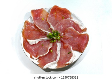 Pork meat slices red color on wooden board, isolated white background with large knife, source of protein, kitchen cuisine ingredients for breakfast, lunch, dinner meal, food preparation for cooking.