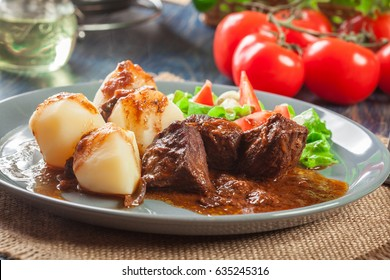 Pork meat stew served with potatoes and vegetable salad on a plate. Side view.