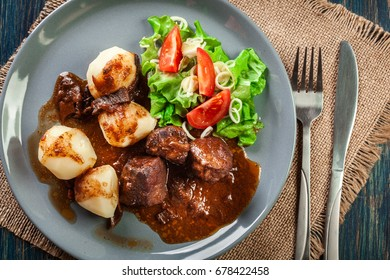 Pork meat stew served with potatoes and vegetable salad on a plate. Top view.