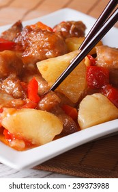 Pork meat with vegetables in sweet and sour sauce on a plate macro. Vertical