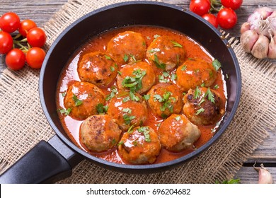 Pork meatballs with parsley in pan .