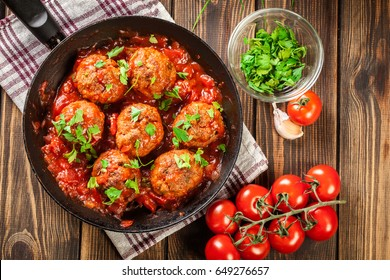 Pork meatballs with spicy tomato sauce on a pan. Top view