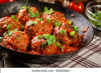 Pork meatballs with spicy tomato sauce on a pan