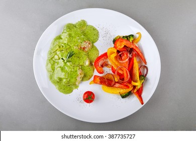 Pork medallions with pesto sauce served on a plate with grelled vegetables. Top view