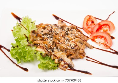 Pork with mushrooms in sauce, tomatoes in white plate, isolate
