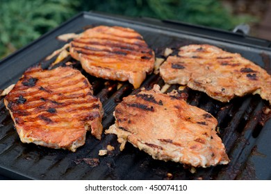 Pork neck fried on small electric grill. Shallow depth of field.
