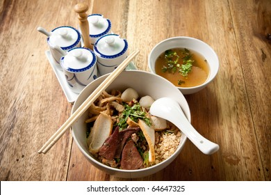 Pork noodle and fish ball with chopstick and spoon on wood background.thai food.