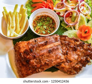 pork rib steak serve on plate / barbecue pork roast french fries fresh vegetable salad and chili sauce spicy - grill spare ribs honey dip