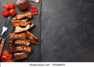 Pork ribs in barbecue sauce and honey roasted tomatoes on a black slate dish. A great snack to beer on a dark stone background. Top view with copy space