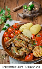 Pork ribs with grilled vegetables and potatoes. Pork ribs stewed in beer sauce