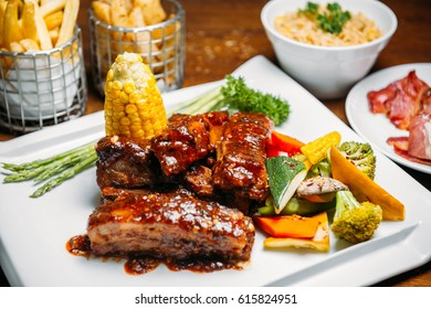 Pork ribs steak with vegetables, corn, rice and fries garnish