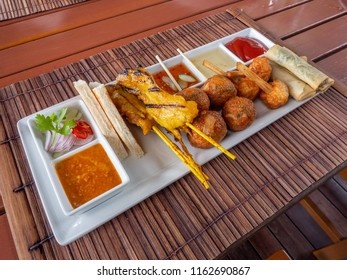 pork satay ,bread ,deep fried spring roll and fried fish-paste balls , snack thai style on wood place mat