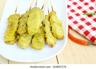 Pork satay on white plates on wooden background