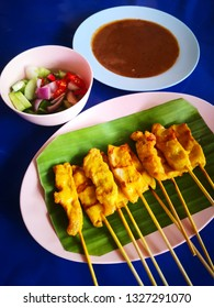 Pork Satay with Peanut Sauce and pickles which are cucumber slices, onions and chilli in vinegar