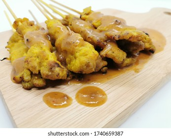 Pork satay is placed on a wooden butcher by taking it from the side corner and white background - Shutterstock ID 1740659387