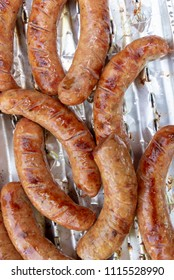 Pork sausages on an aluminium tray on a grill. Top view