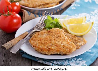 Pork schnitzel with lemon wedges in pan