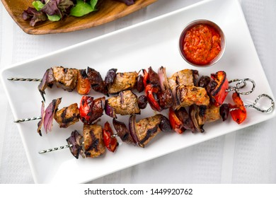 Pork shish kabob skewers viewed from above. These delicious pork meat souvlaki were roasted on the bbq until well-grilled. Cooking food on skewers has been common in many cuisines since ancient times.