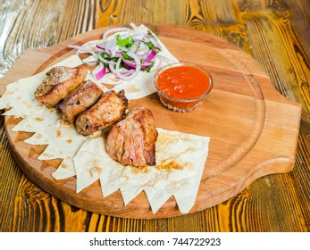 pork shish kebab with onions and pita bread