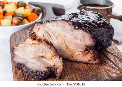 Pork shoulder in honey parmesan and soy souse, prepared in slow cooker or crockpot, on a wooden board, horizontal