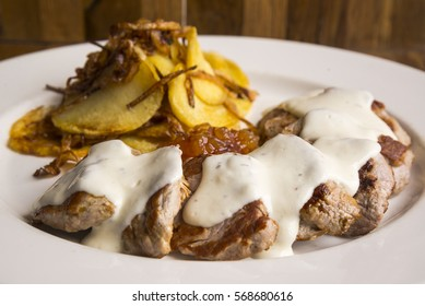 Pork sirloin with cheese sauce and garnish