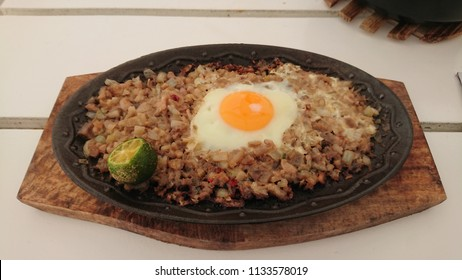 Pork Sizzling Sisig. Filipino Cuisine made  from parts of pig head and liver, usually seasoned with calamansi and chili peppers.