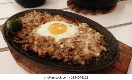 Pork Sizzling Sisig. Filipino Cuisine made  from parts of pig head and liver, usually seasoned with calamansi and chili peppers. Perspective shot.