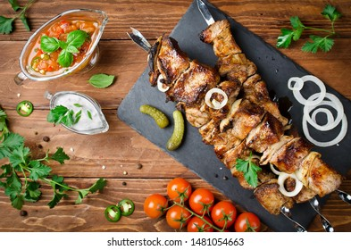 Pork skewers with onions on a wooden table. Barbecuing lunch
