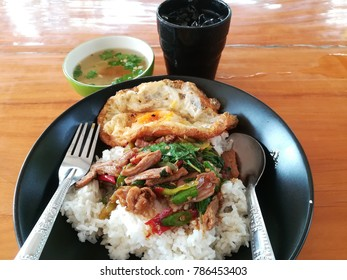 Pork sliced with sweet basil leaves served with fried egg and streamed rice.