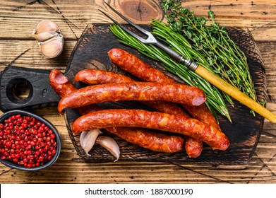 Pork Smoked sausages with addition of fresh aromatic herbs and spices. wooden background. Top view.