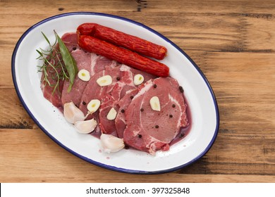 pork with smoked sausages and garlic on dish on brown wooden background