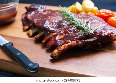 Pork Spareribs with tomato and fried potatoes on wooden plate served with BBQ sauce
