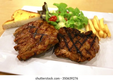 pork stake with french fried ,juicy grilled pork chop (neck cut) with greens