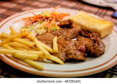 Pork steak with black pepper ,salad ,french fried