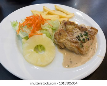 Pork steak with Black pepper sauce with salad frenfried and Pineapple